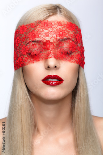 Woman face with eyes closed by red ribbon