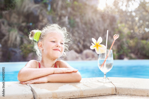 toddler girl with cocktail in tropical beach pool