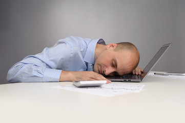 Businessman sleeping on a laptop