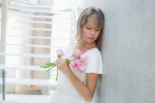 Beautiful sad young woman with flowers