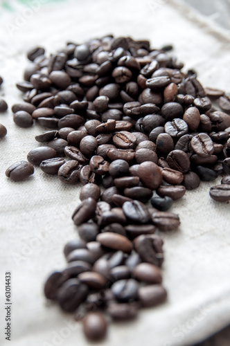 Roasted coffee beans over rustic background.