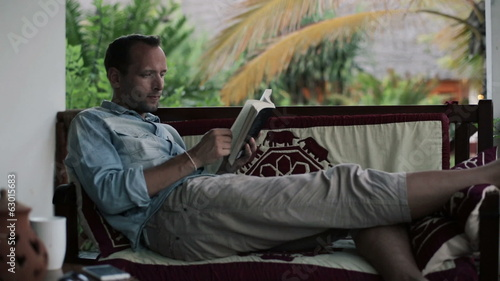 Young man on sofa reading book on patio