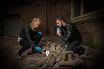 Detectives investigate the crime scene