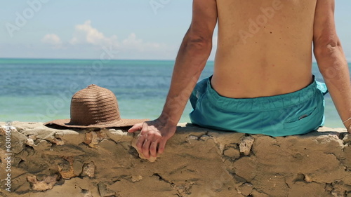 Man sitting and relaxing on stone wall by exotic sea