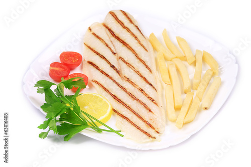 Fried fish fillet with fries and vegetables.