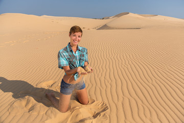 woman sitting on the beach in the sand dunes with sand in hands
