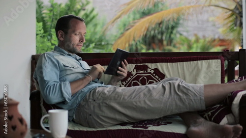 Man with tablet computer drinking coffee on country house porch