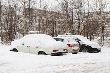 Cars under snow on parking