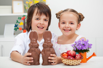 Happy kids with chocolate bunnies and other easter items