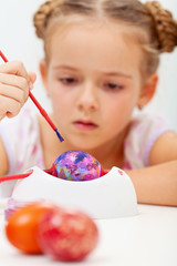 Little girl painting an artsy easter egg