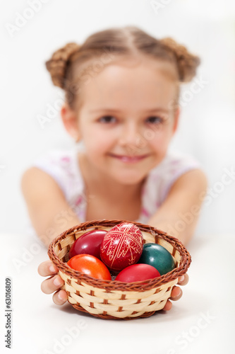 Little girl holding a basket with dyed and decorated easter eggs