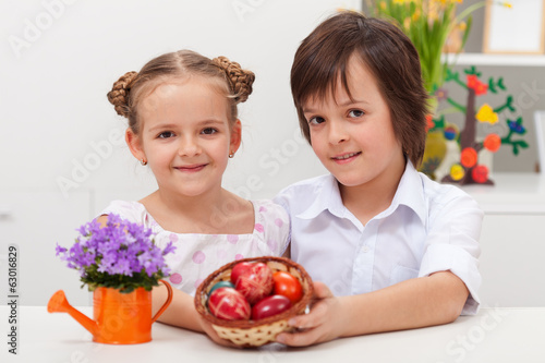 Kids dressed for celebration holding dyed easter eggs