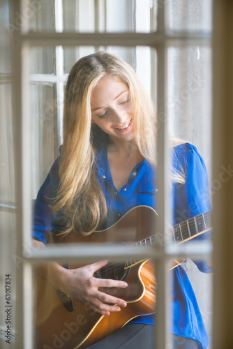 Young woman playing guitar on window