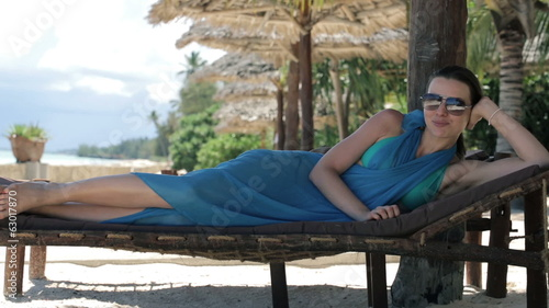 Portrait of happy sexy woman lying on sunbed in exotic resort