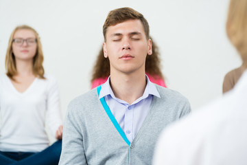 young man, meditating with closed eyes