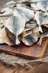 Close-up of dried scad fish on a cutting board, vertical shot