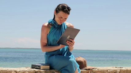 Woman with tablet computer sitting on wall by the sea