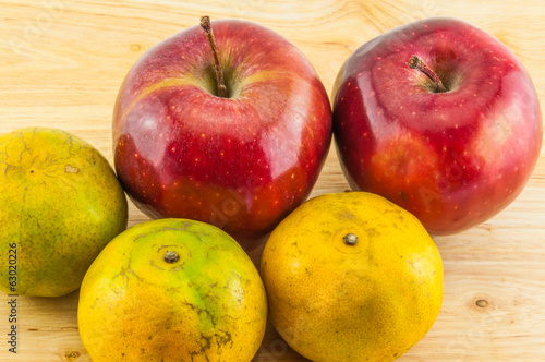 Apple & tangerine on wood background