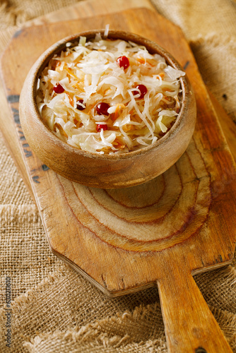 sauerkraut - Sour cabbage -  on wooden bowl with crunberry