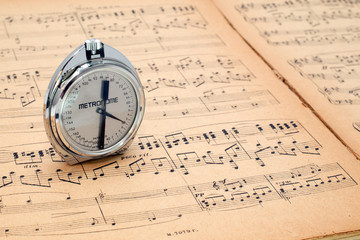 Pocket metronome  on an ancient music score background