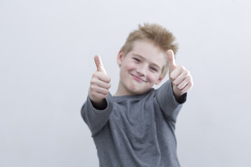 Boy (10-11) showing thumbs up sign, smiling, close-up