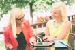 Two Women Using Digital Tablet at Bar