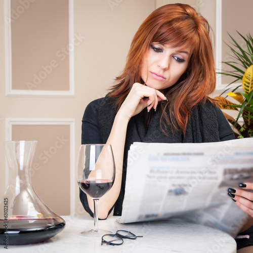 Young redhead woman reading newspaper with a glass of wine insid
