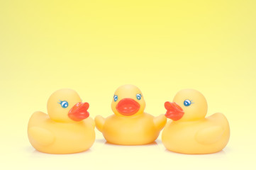 Tres patos reunidos sobre fondo amarillo