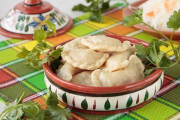 Ceramic bowl wiht dumplings on checkered napkin