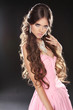 Wavy Hair. Beautiful Sexy Brunette Woman in pink dress. Healthy