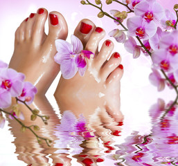 Wet feet with orchid above the water.