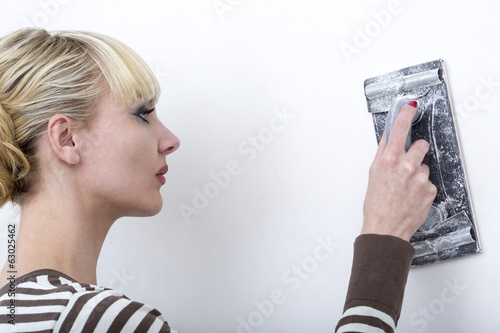 Woman, smooths out hard putty on a wall an emery paper