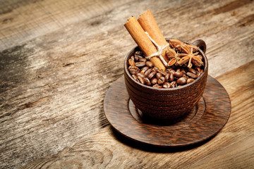 Wooden cup with coffee-beans on wooden table