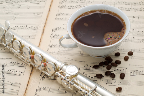 Silver flute,cup of coffee on an ancient music score background