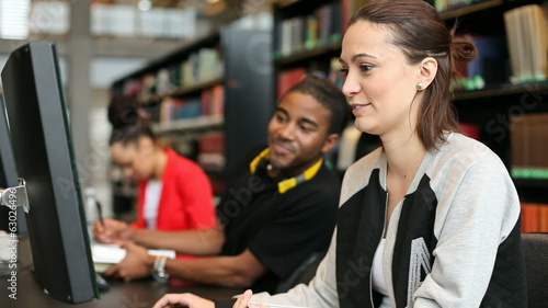 University students studying in library with computers