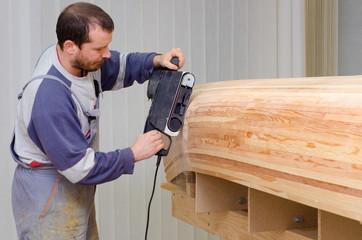 Young carpenter sanding new canoe in workshop