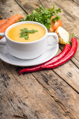 Organic food. Pea soup with vegetables around on wood background