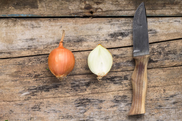 Onion whole and cut in half with knife on wood background