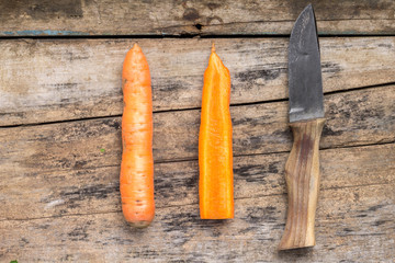 Carrot whole and cut in half with knife on wood background