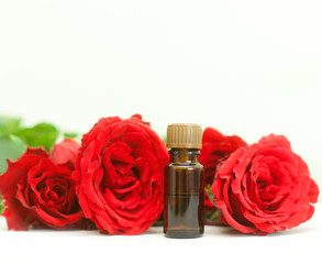bottle of aromatherapy oil and bright red roses, beauty spa