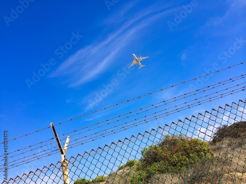Airplane Flying Over Airport Fence