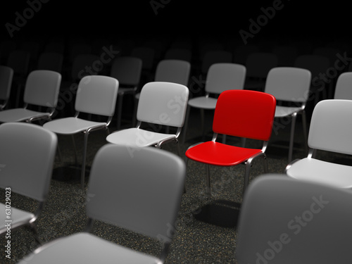Group of chairs with a red chair standing out