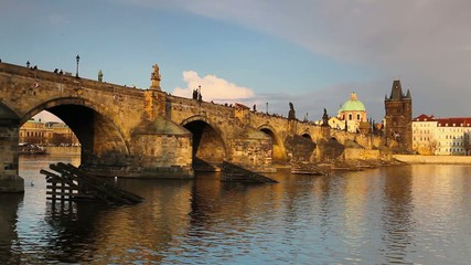 Famous Charles bridge on Vltava river in Prague at sunset