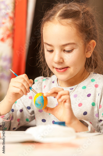 Closeup portrait of girl painting easter eggs