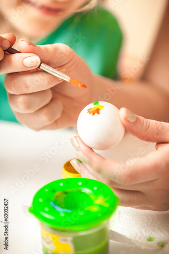 Closeup shot of woman and girl drawing flowers on easter eggs