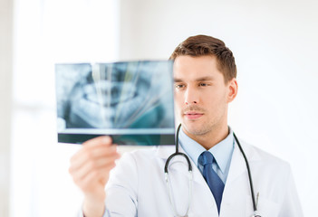 concerned male doctor or dentist looking at x-ray