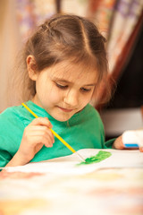 Portrait of young schoolgirl drawing with watercolors