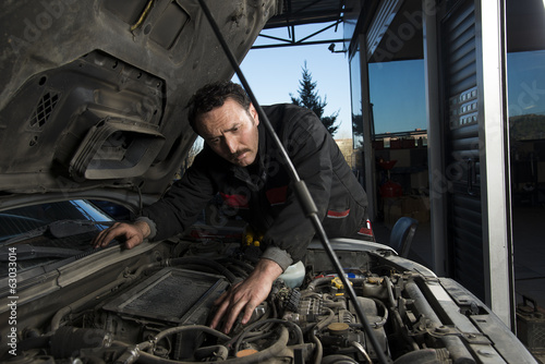 Auto repairman fixing an old car