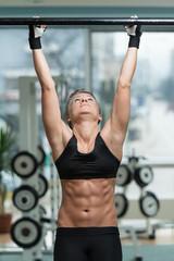 Fitness Woman Performing Hanging Leg Raises Exercise