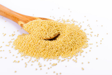Millet in a wooden spoon
